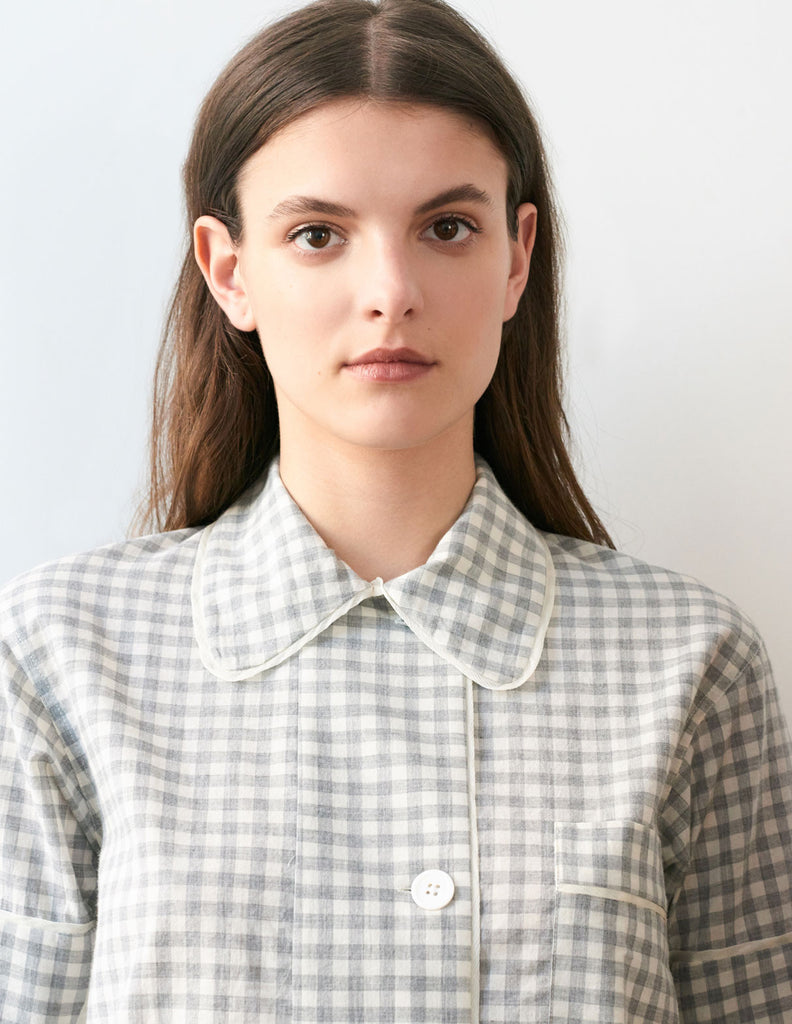 Close up, woman wearing light grey cotton collared short-sleeved sleep shirt with left breast pocket and contrast piping