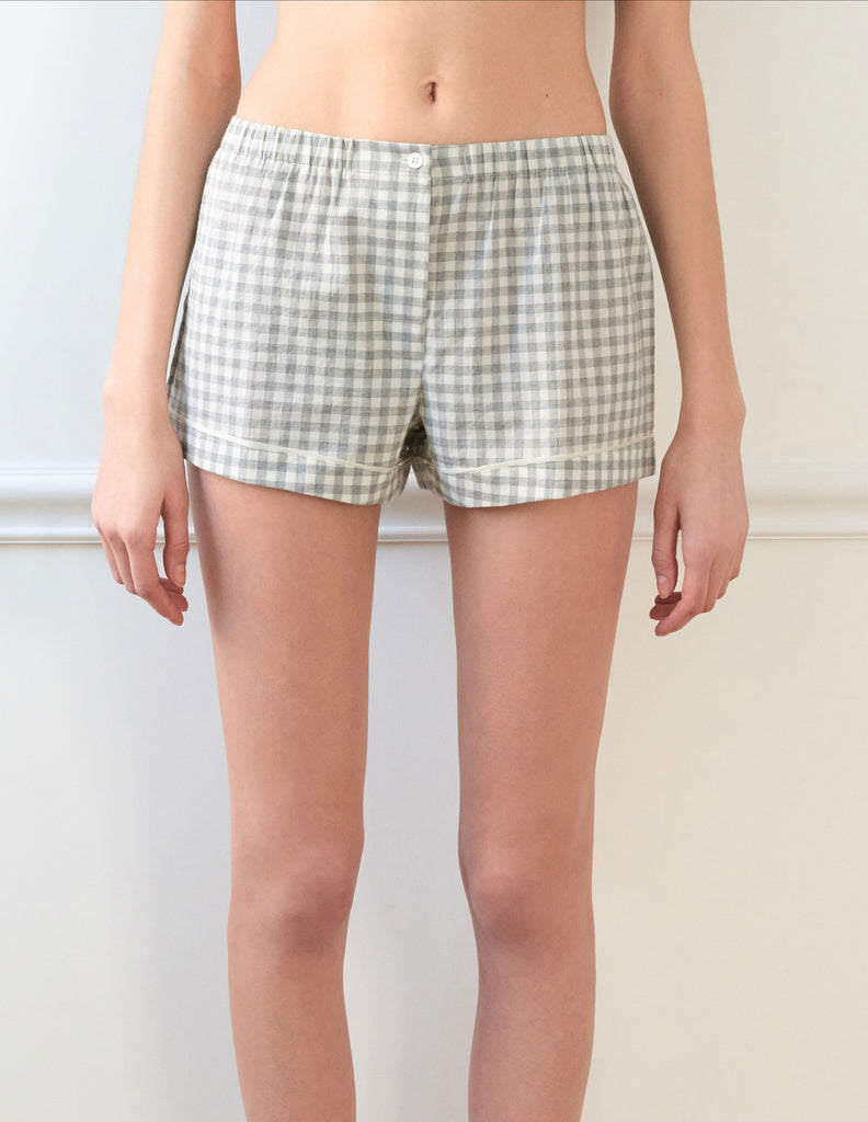 Woman wears light grey cotton boxer shorts with contrast piping