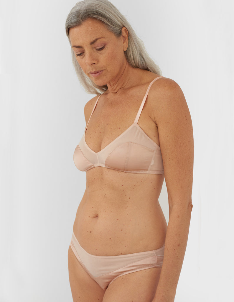 Front view of woman wearing beige panty and matching bralette.