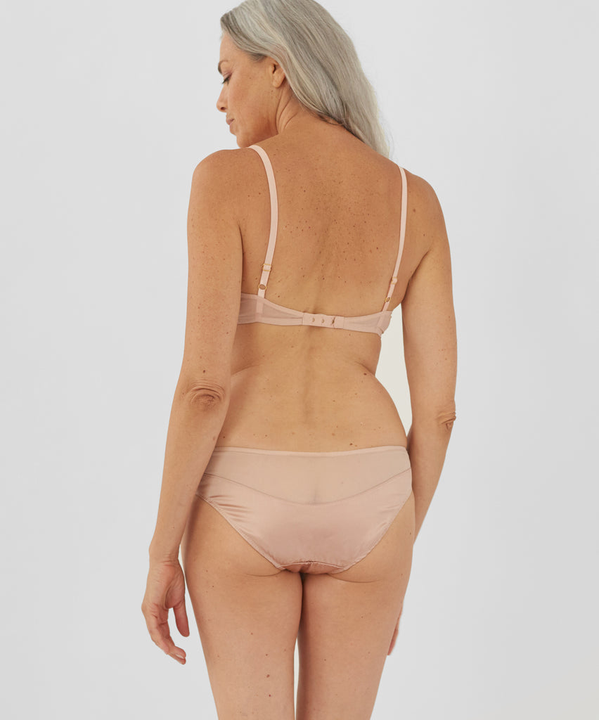 Back view of woman wearing beige panty and matching bralette.