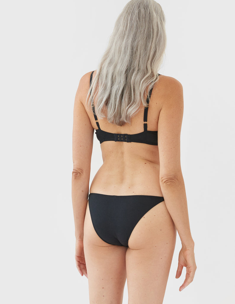 back of Woman wearing black bra and matching string panty
