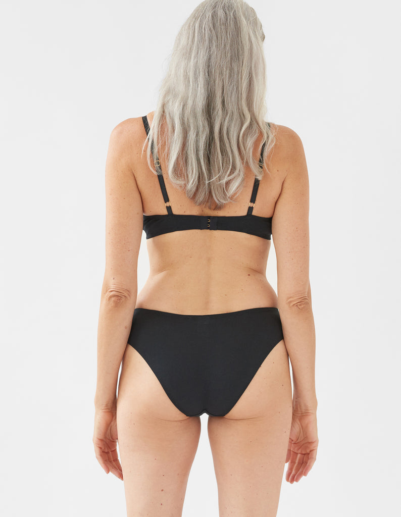 back of Woman wearing black bra and matching panty