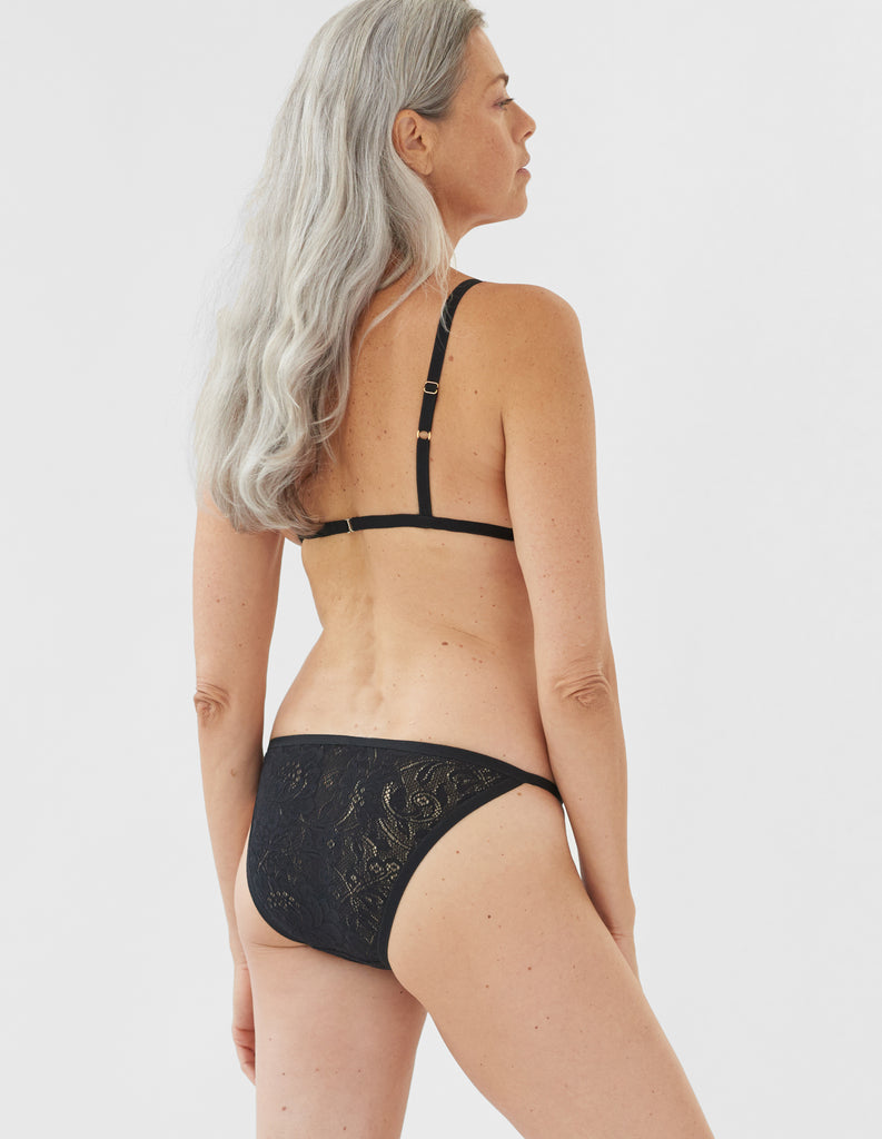 Woman wearing black lace triangle bra and matching string panty.