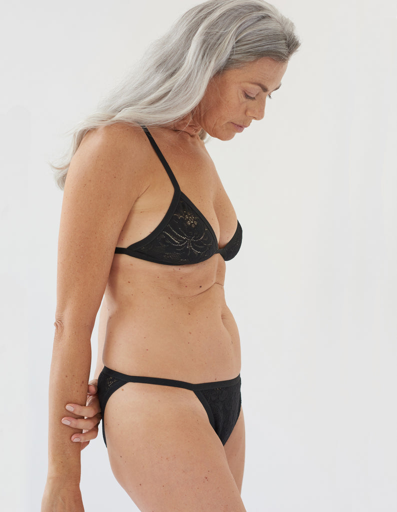 side of woman wearing black lace triangle bra and matching string panty
