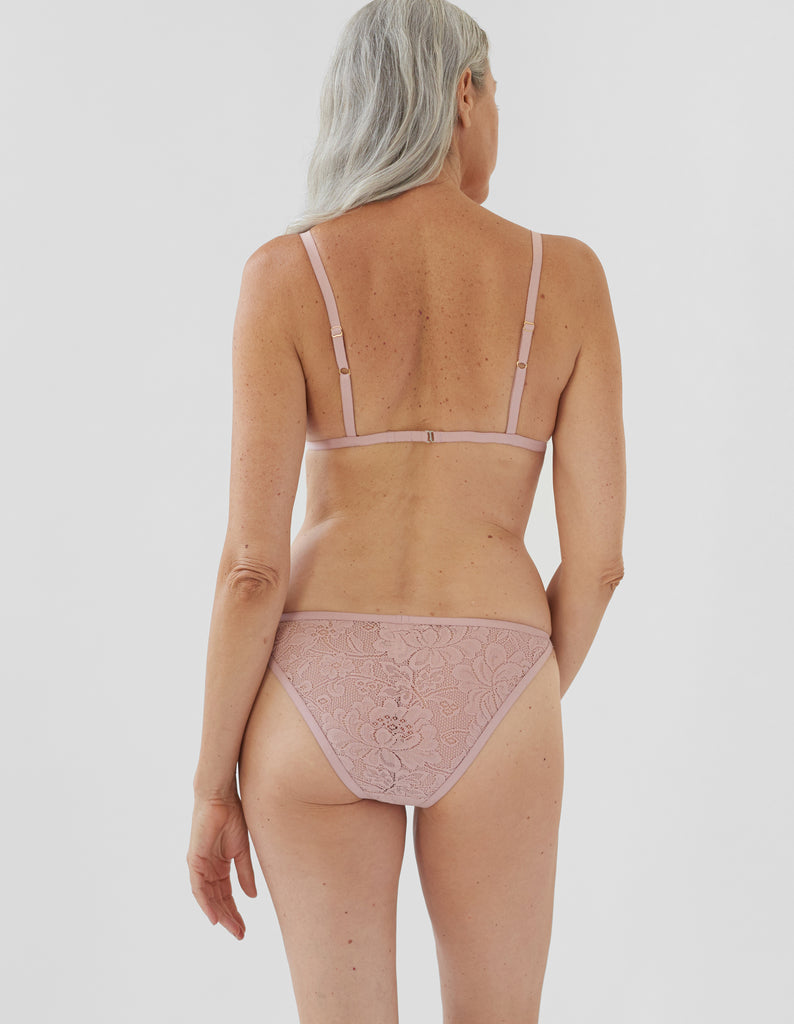 back of woman wearing beige lace triangle bra and matching string panty