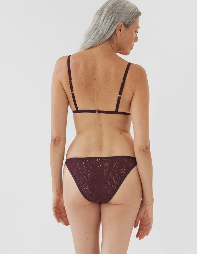 back of woman wearing dark red lace triangle bra and matching string panty