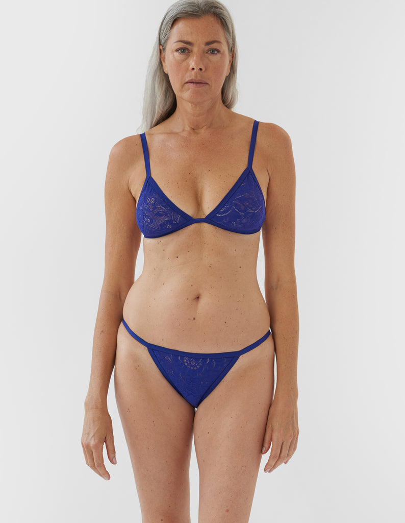 woman wearing blue lace triangle bra and matching string panty