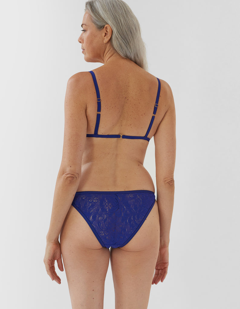 back of woman wearing blue lace triangle bra and matching string panty
