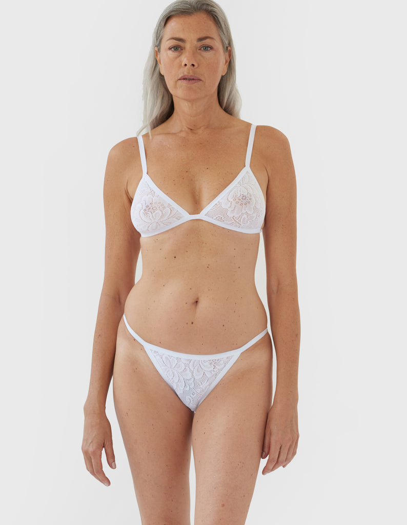 woman wearing white lace triangle bra and matching string panty