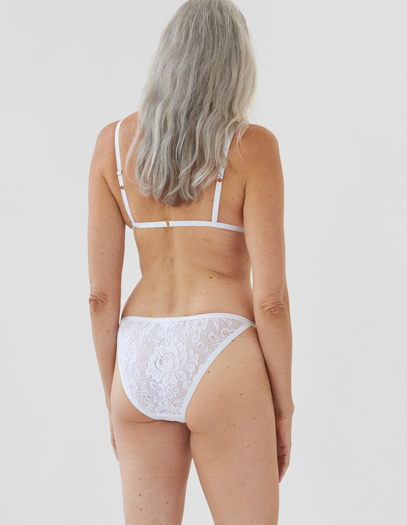 back of woman wearing white lace triangle bra and matching string panty