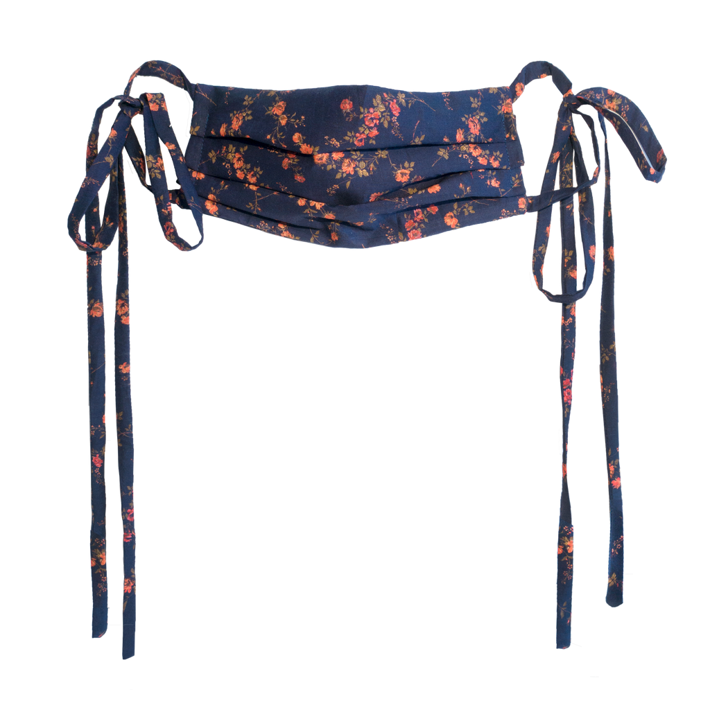 A cotton printed face mask made from printed cotton with red and orange flowers, peach, purple, and green leaves. The masks have ties on each side.