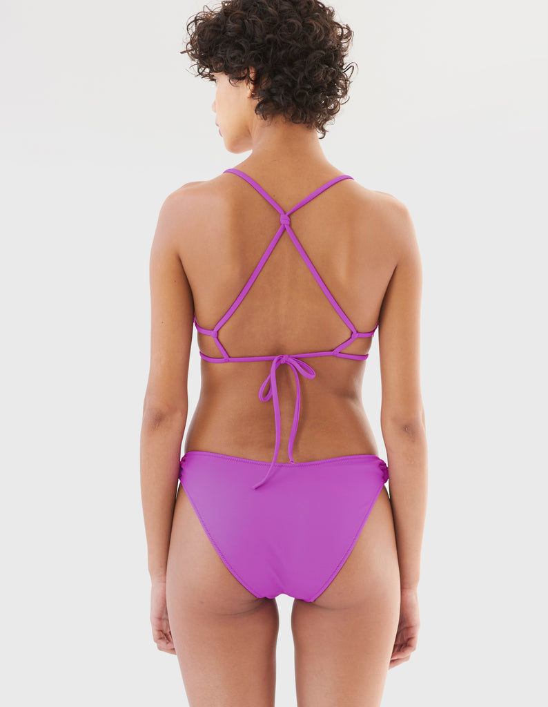 back view of women in purple string bikini top and matching bottom