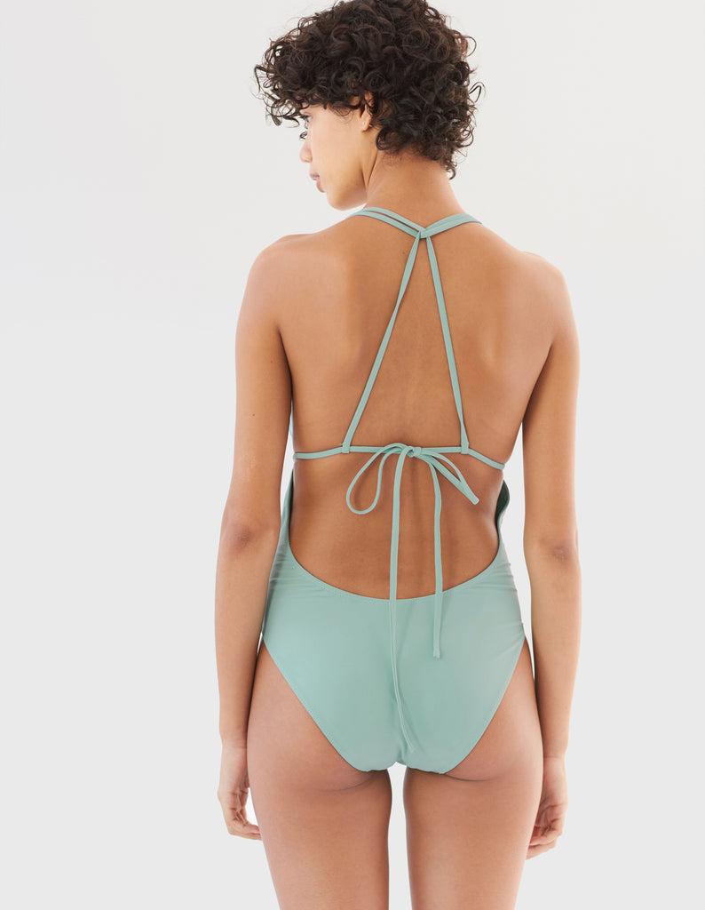 woman in blue one piece swimsuit with string back by Araks