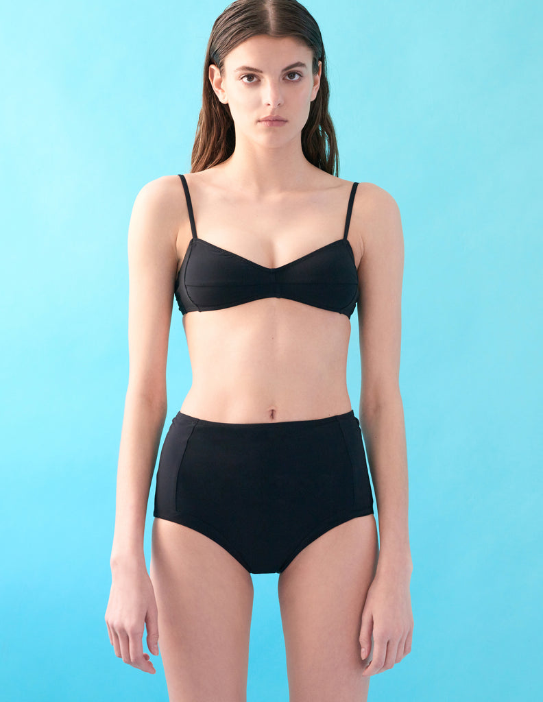 Front view of model wearing black bralette and matching panty.