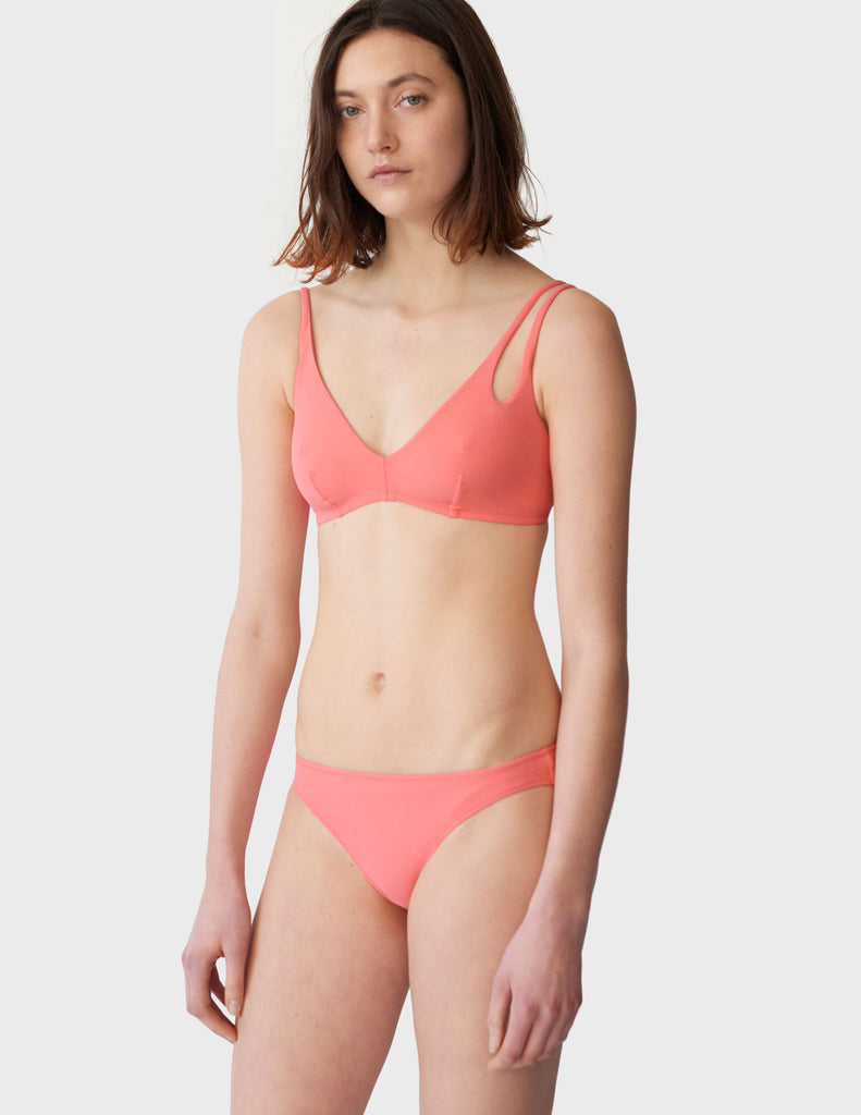 Woman wearing peach low-rise swim bottoms with matching bikini top with asymmetrical crisscross strap.