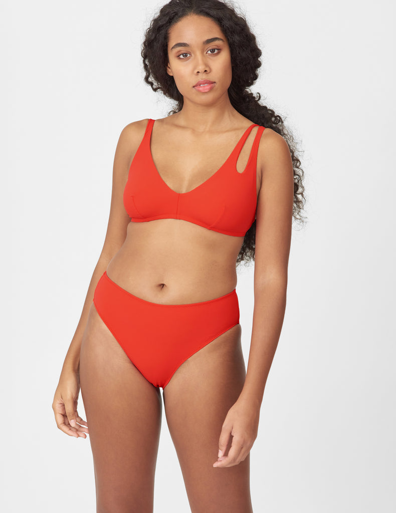 Front view of woman wearing a red bikini top with asymmetric crisscross straps with matching bottoms
