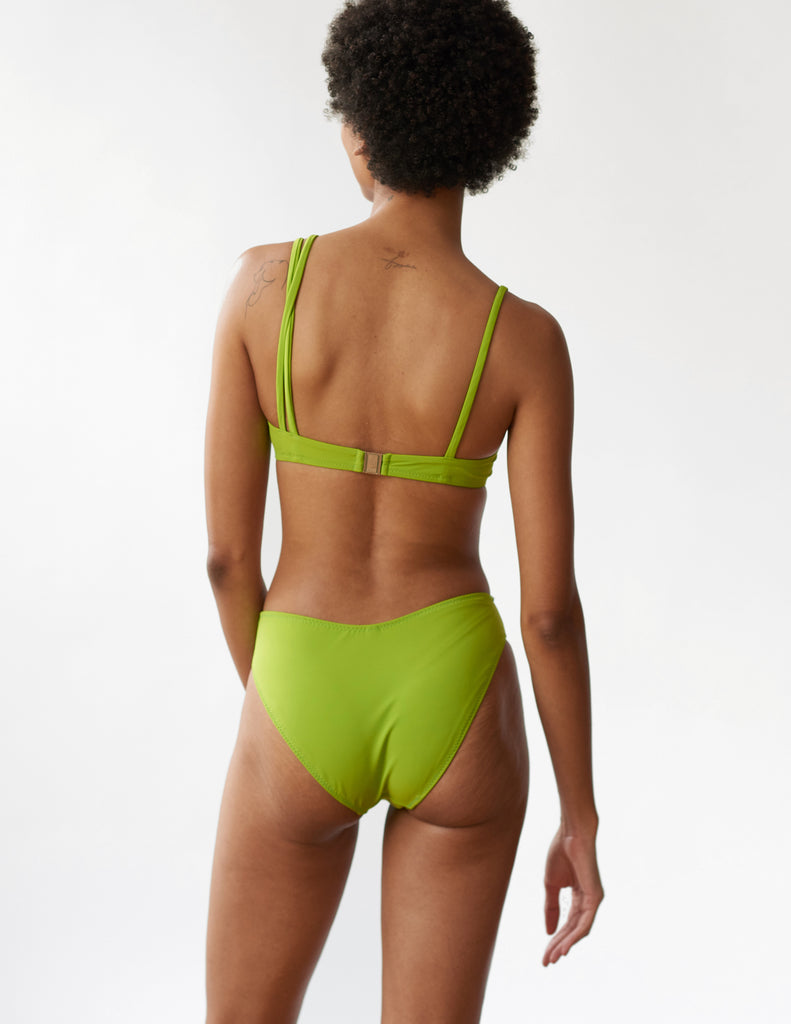 back of woman wearing green bikini top with asymmetric straps and matching bottoms