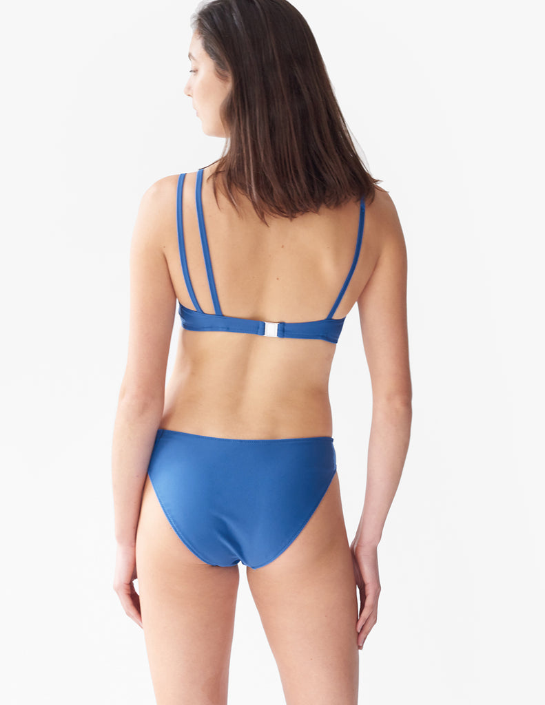 Back view of woman wearing a blue bikini top with asymmetric crisscross straps with matching bottoms