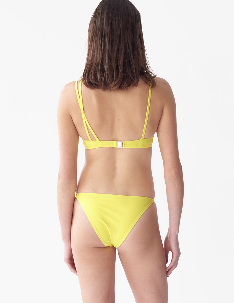 Back view of woman wearing an yellow bikini top with asymmetric crisscross straps with matching bottoms