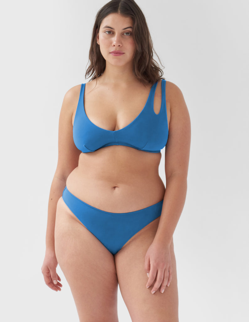 Woman wearing a blue mid-rise swim bottoms with matching bikini top