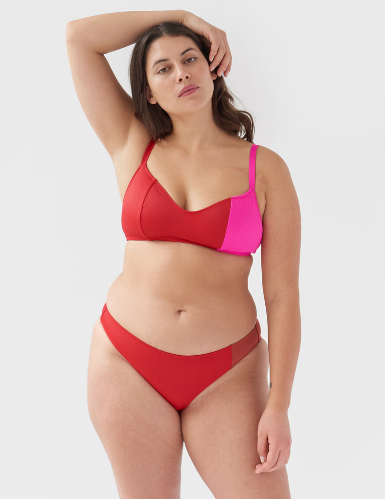 Woman wearing an asymmetrical color-blocked pink and plum low-rise bikini bottom with matching color-blocked bikini top