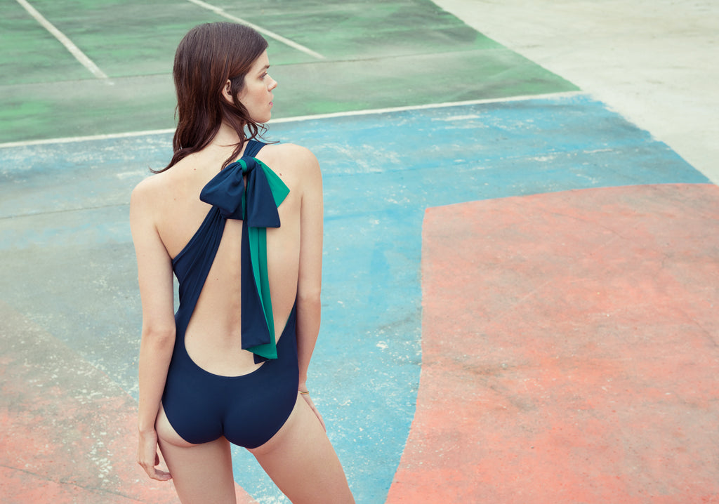 Back shot of woman wearing blue and green one-piece.  Edit alt text