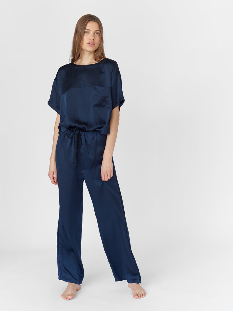 Woman wearing Navy silk boat neck sleep shirt with left breast pocket and matching silk pants