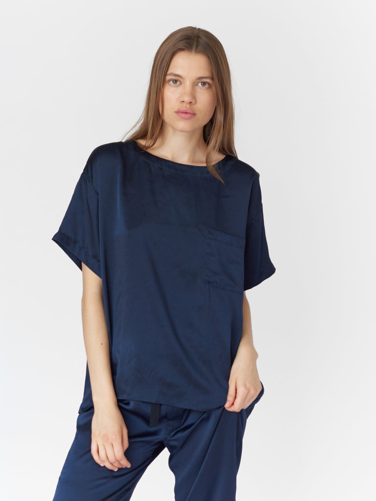 Close up, woman wearing Navy silk boat neck sleep shirt with left breast pocket and matching silk pants