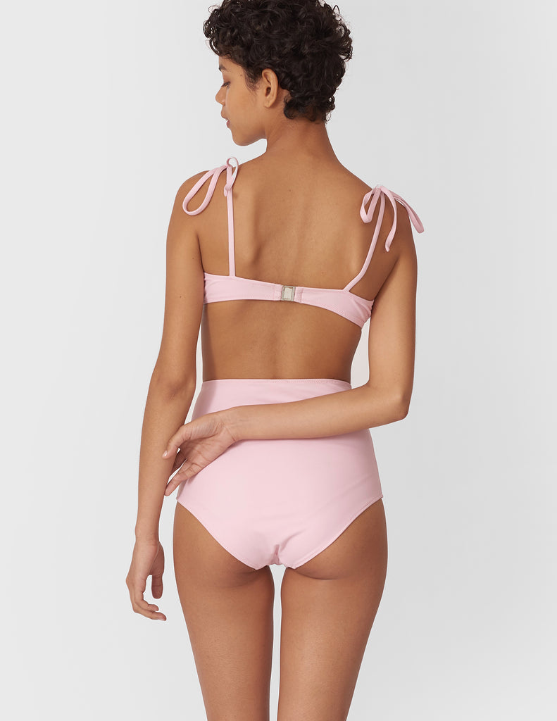 Back shot of woman wearing a light pink high-waisted swim bottoms with matching underwire bikini top.