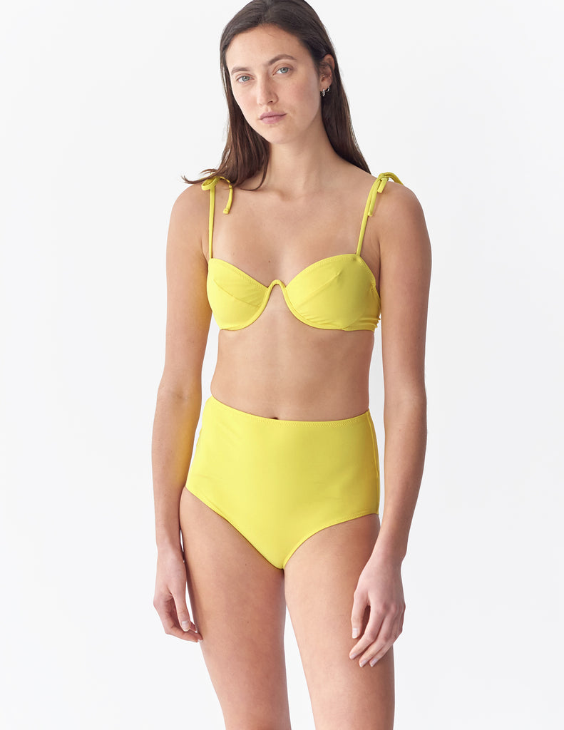 Front view of a woman wearing a yellow underwire bikini top with matching bottoms