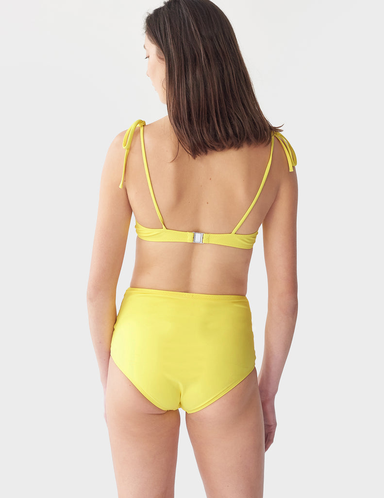 Back view of a woman wearing a yellow underwire bikini top with matching bottoms