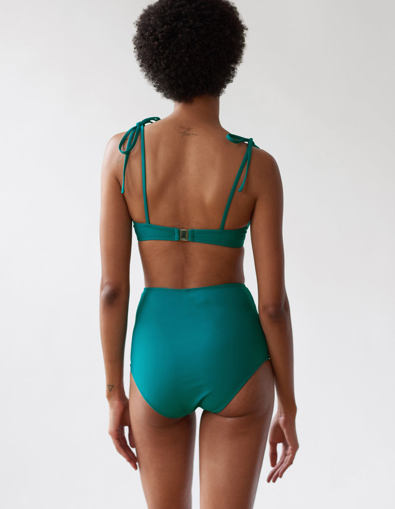 back of A woman wearing an underwire bikini top and matching high waisted bottom in teal.