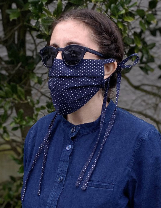 Woman wearing cotton printed face mask made from printed navy cotton with white polka dots. The masks have ties on each side.