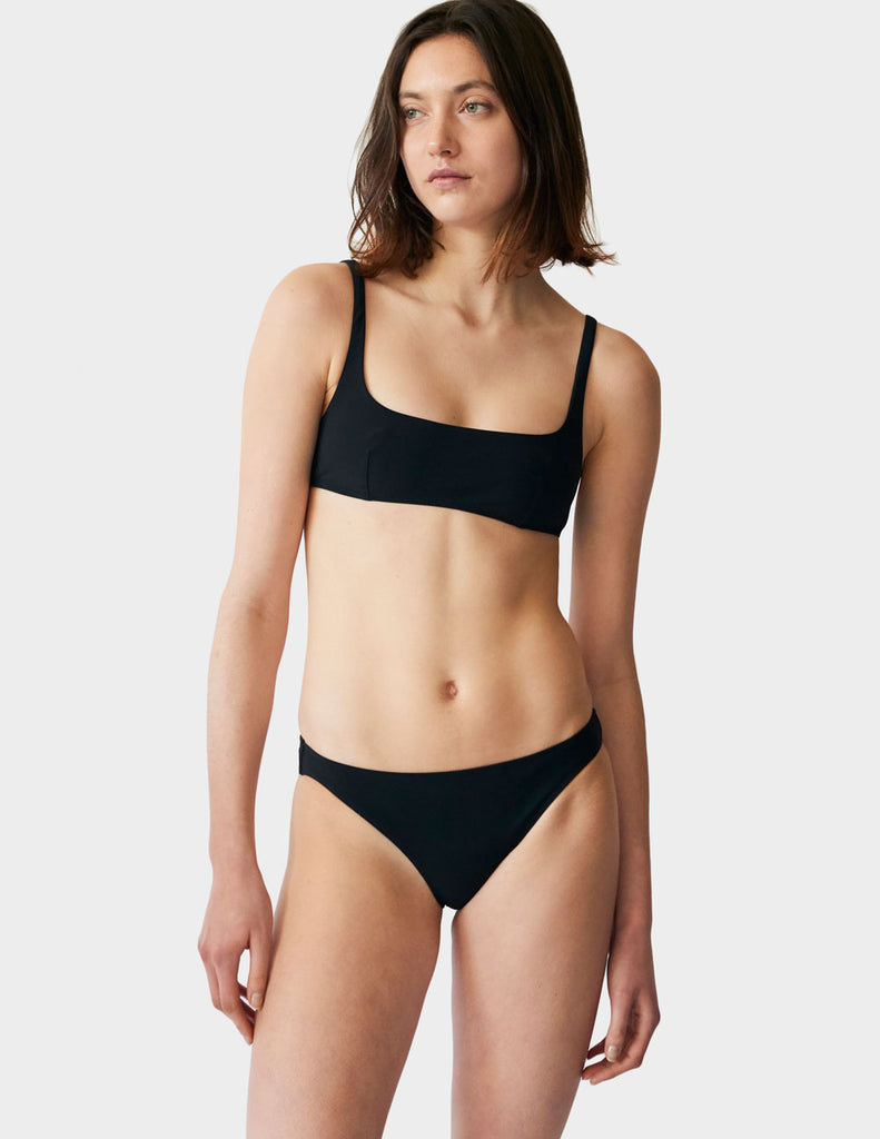 Woman wearing black low-rise bottoms with matching black wide scoop neck bikini top.