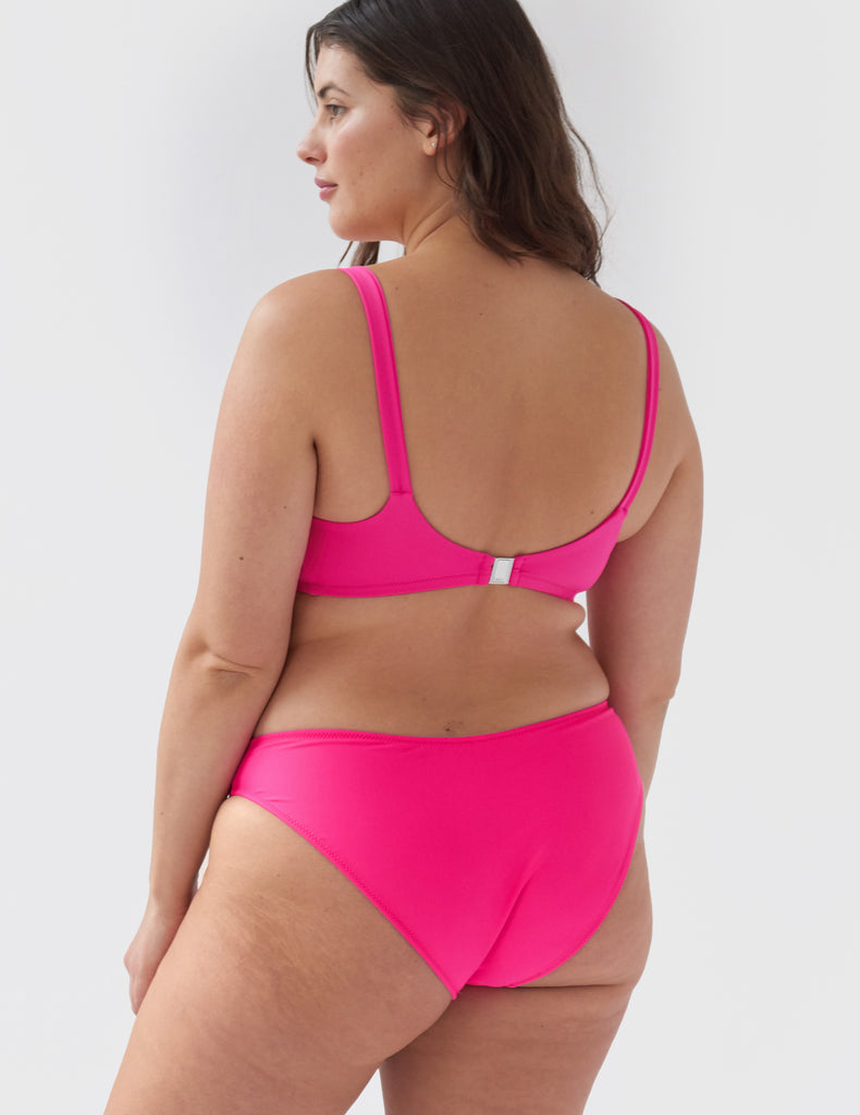 Woman wearing a hot pink high-waisted bikini bottom with side seams with matching scoop neck bikini top
