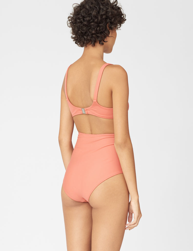 Back view of woman wearing a pink high-waisted bikini bottom and matching bikini top