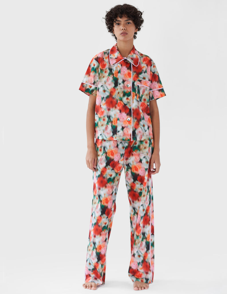 woman wearing red floral print cotton pajama top with collar and buttons and matching pants