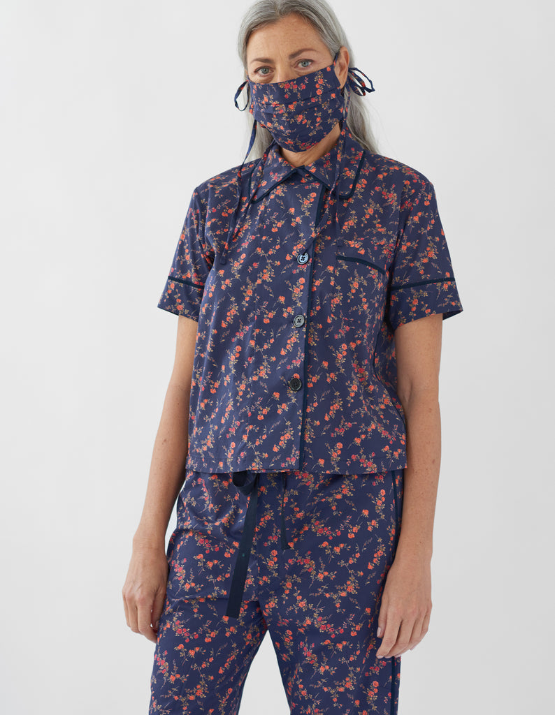 woman wearing navy floral pajama top and matching pants and face mask