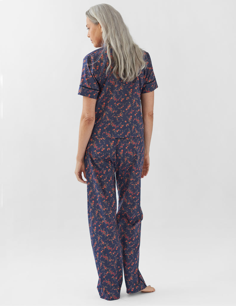 back of woman wearing navy floral pajama top and matching pants