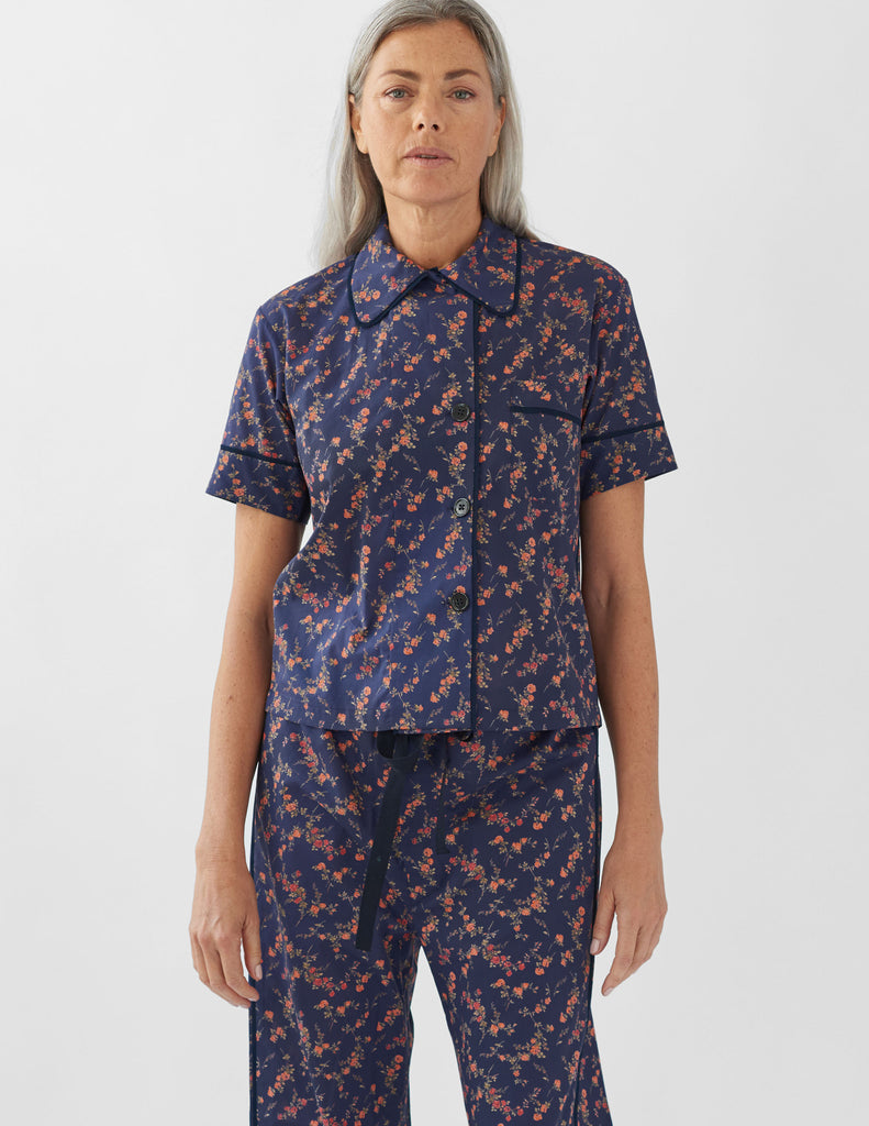 woman wearing navy floral pajama top and matching pants
