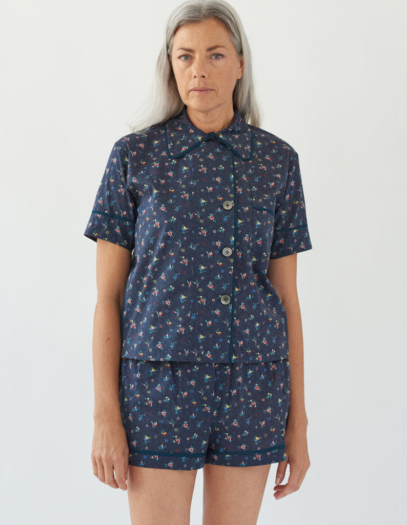 woman wearing navy floral pajama top and matching shorts