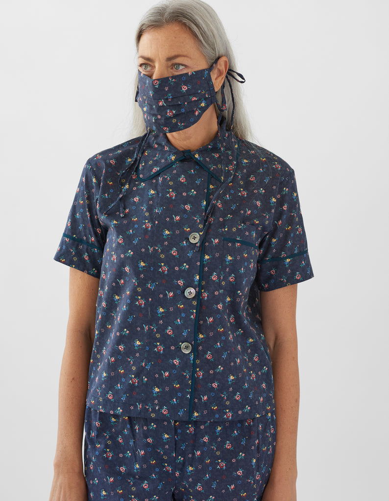 woman wearing navy floral pajama top and matching shorts and face mask