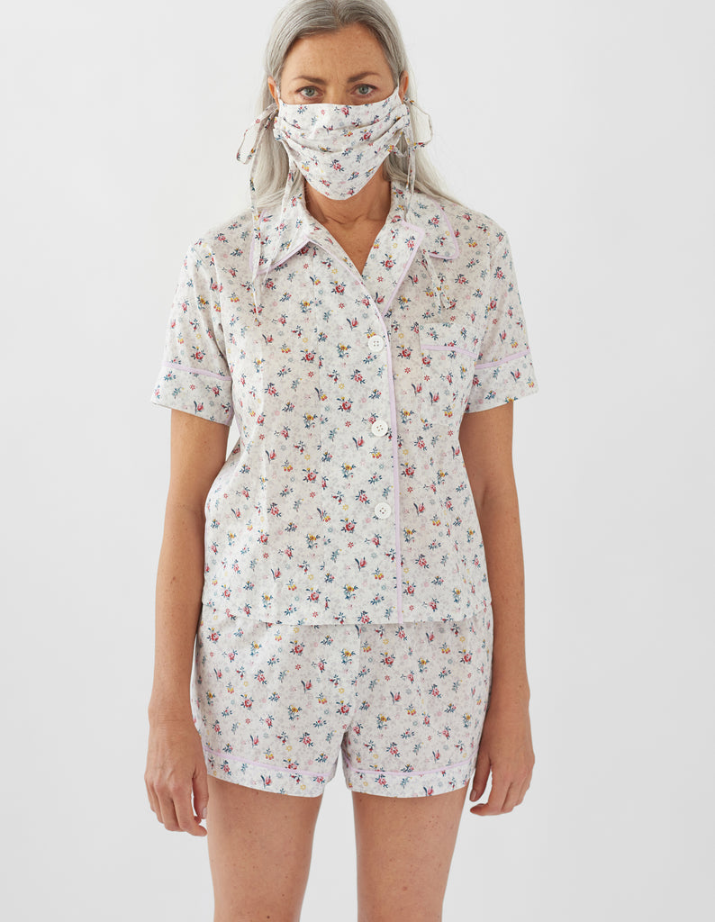Woman wearing white floral print pajamas and Cotton face mask made from printed fabric. The design is white with red and yellow flowers