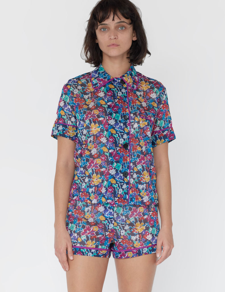 Woman wearing blue based with multicolor floral cotton boxer shorts with contrast piping with matching collared sleep shirt