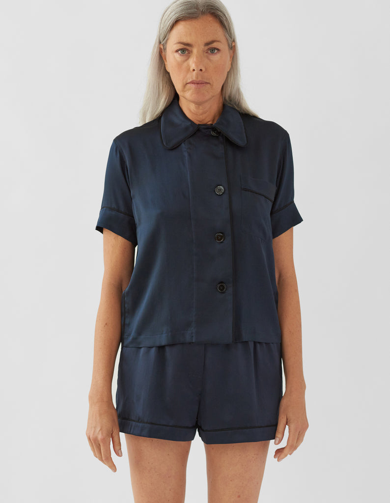 Woman wearing navy silk collared short-sleeved sleep shirt with left breast pocket and contrast piping and matching shorts