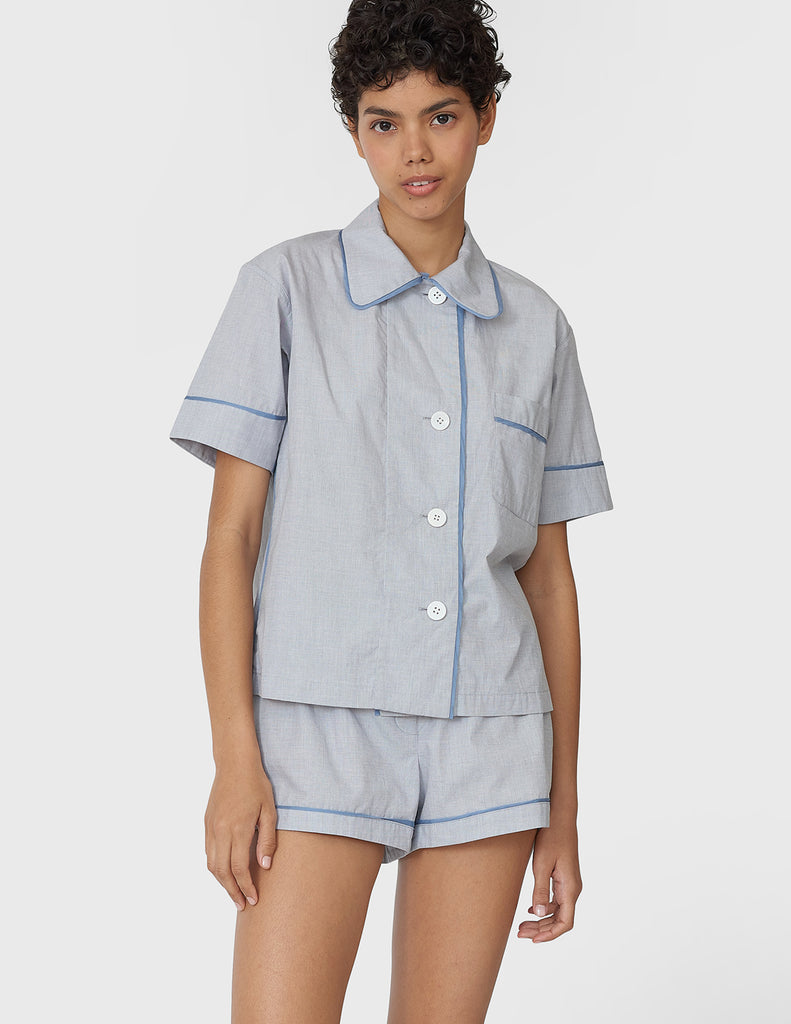 Woman wearing light blue cotton collared short-sleeved sleep shirt with left breast pocket and contrast piping and matching shorts
