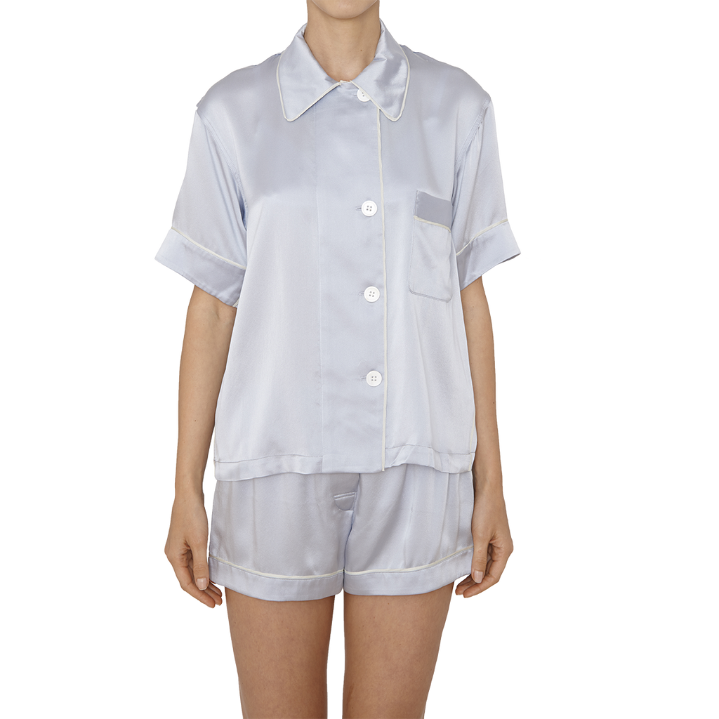 Woman wearing light grey silk collared short-sleeved sleep shirt with left breast pocket and contrast piping and matching shorts