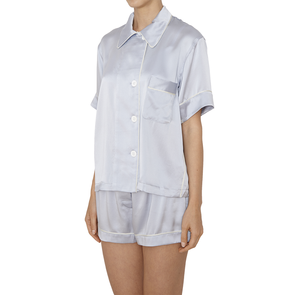 Woman's side, wearing blue silk collared short-sleeved sleep shirt with left breast pocket and contrast piping and matching shorts