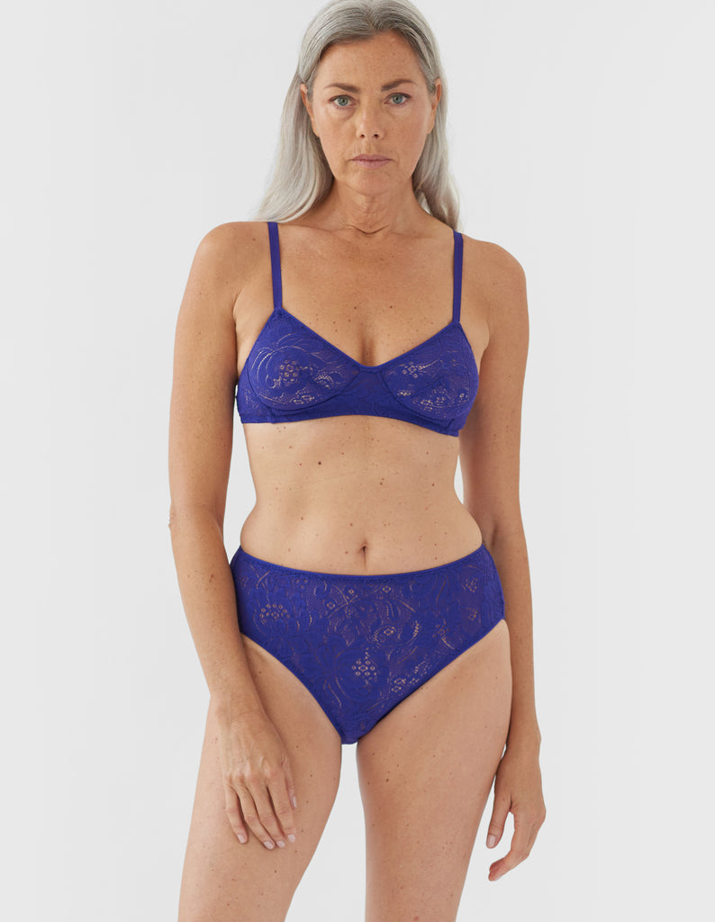 Front view of woman wearing blue lace panty with matching bralette