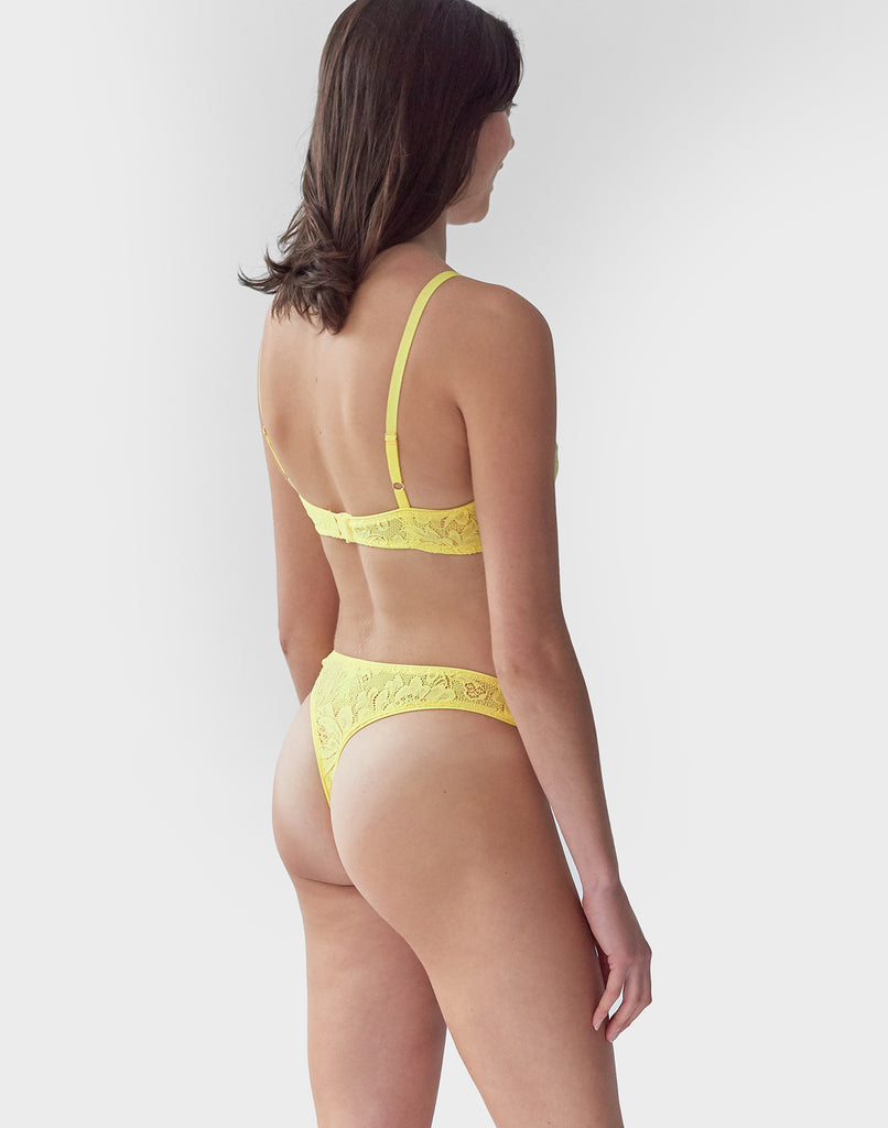 Face away, woman wearing Yellow, lace wireless bralette with matching straps, and matching Thong.